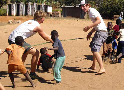 Volunteers and local kids playing tug of war