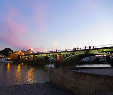 A view of the Triana bridge at sunset in Sevilla.