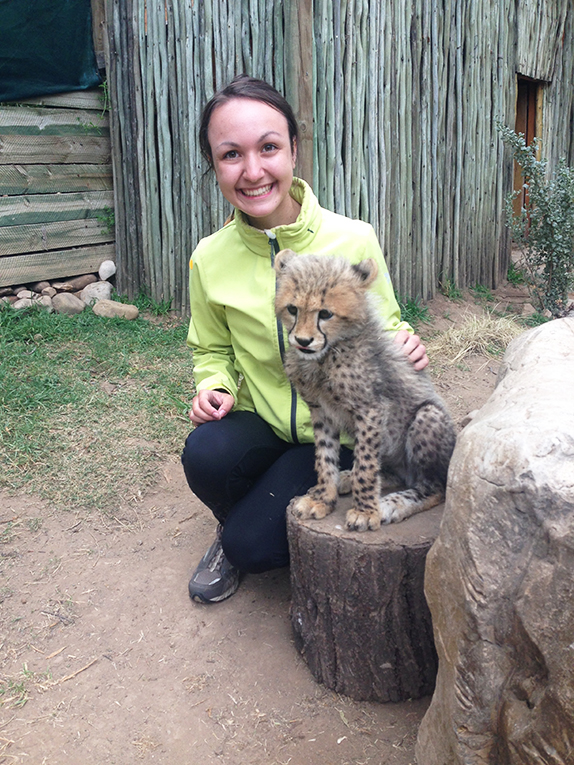Volunteer with a cheetah cub in South Africa