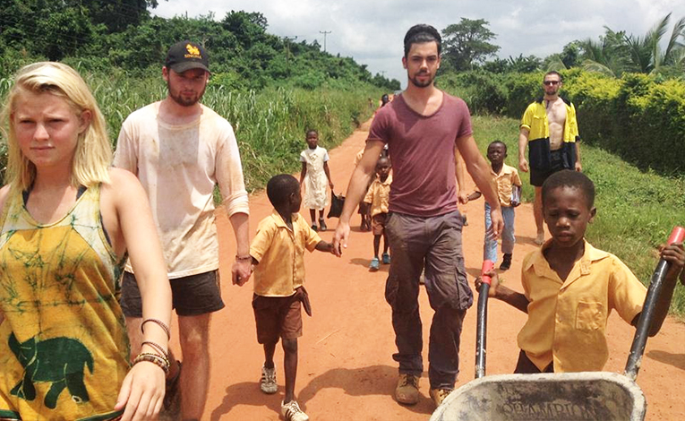 Volunteers walking with children in Assin Asempaneye, Ghana