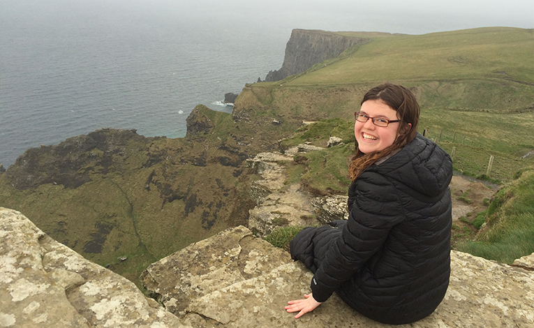 Girl sitting on the edge of the Cliffs of Moher in Ireland
