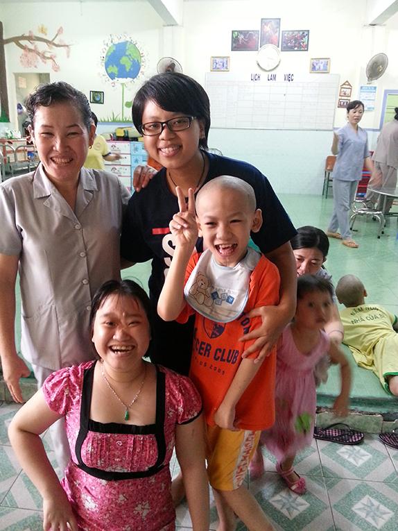 Volunteer with orphanage staff and children in Vietnam