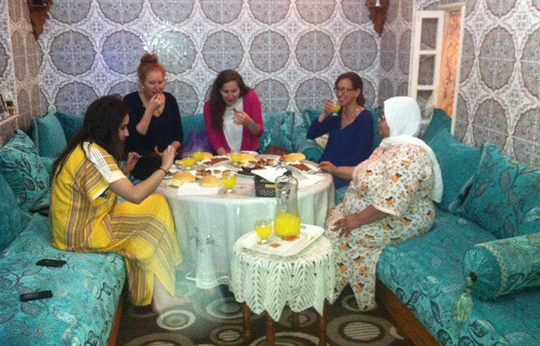Study abroad students eating dinner with their host family in Morocco