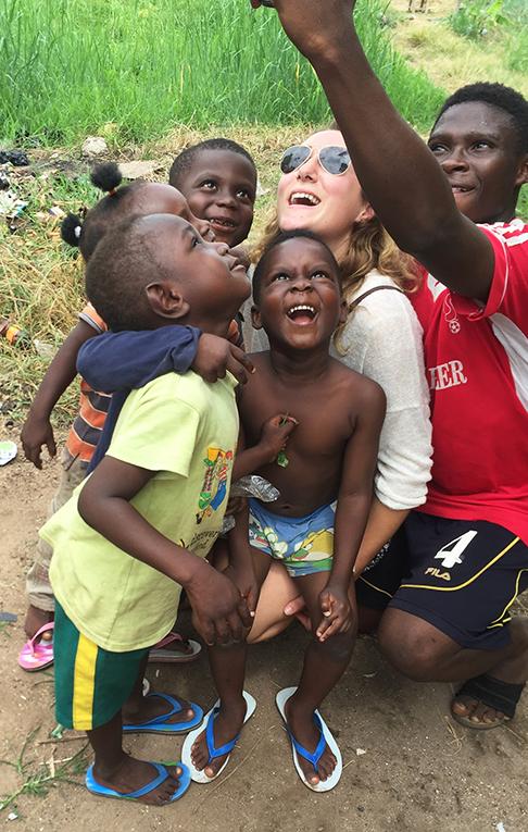 Volunteer taking selfies with Ghanaian orphans