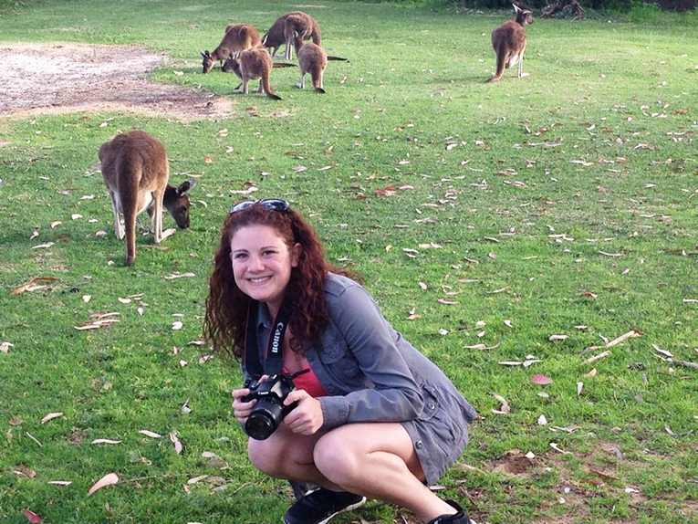 Students posing by kangaroos in Australia