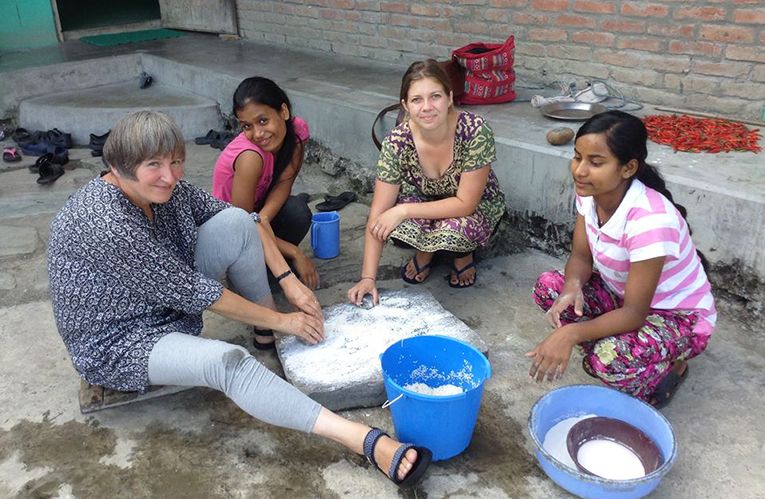 Volunteers making rice flour at a childrens home in Nepal