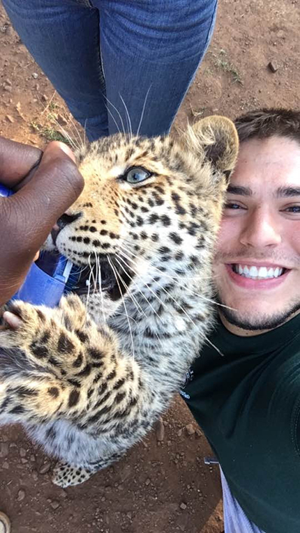 Volunteer with leopard cub in South Africa
