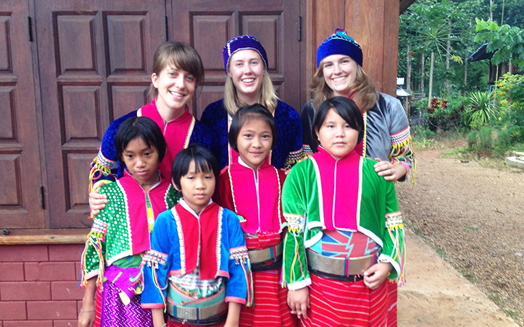 Tourists with local children dressed for Palaung festival in Chiang Dao, Thailand