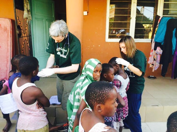 Volunteers give orphans health exams in Tanzania