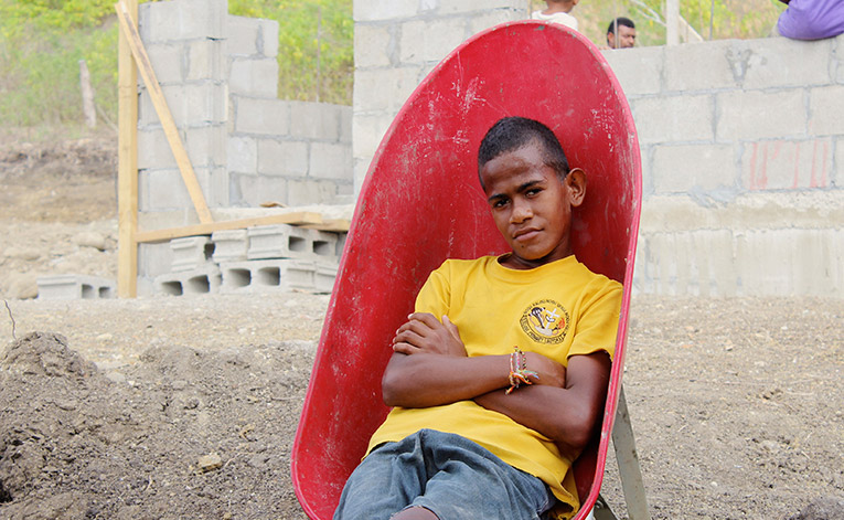 Fijian youth sitting in a wheelbarrow
