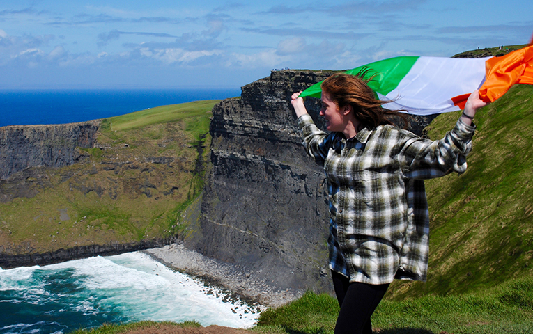 Girl holding the Irish flag at the Cliffs of Moher, Ireland