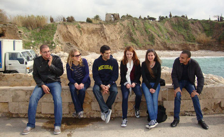 Friends sitting along the coast in Byblos, Lebanon