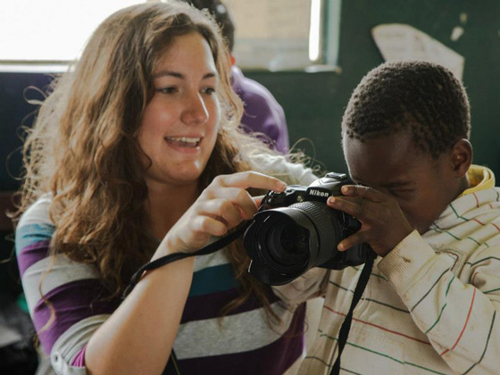 female volunteer teaching a child how to capture a photo