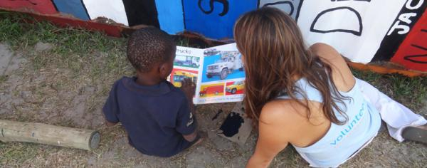 A volunteer and a child reading a book about cars