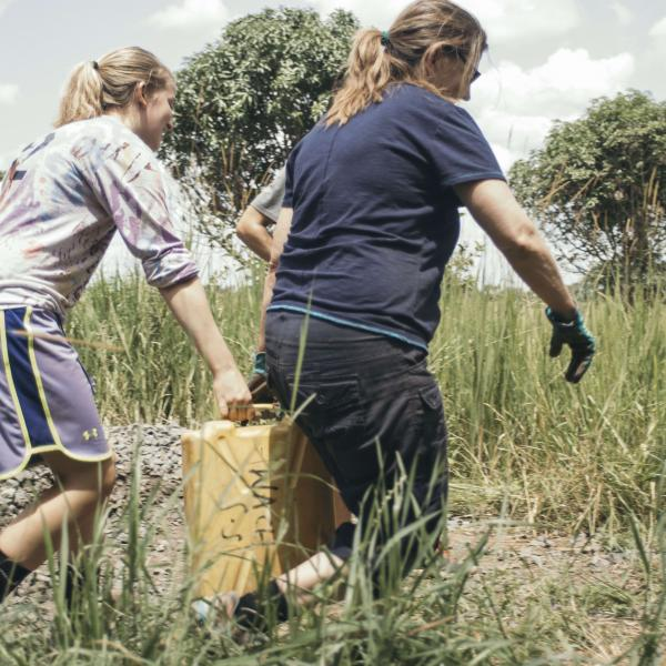 Volunteers Carry Water in Uganda. Africa, to help mix cement for plastering school structures.