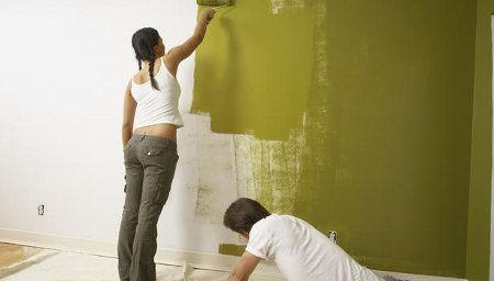 Volunteers painting a wall green