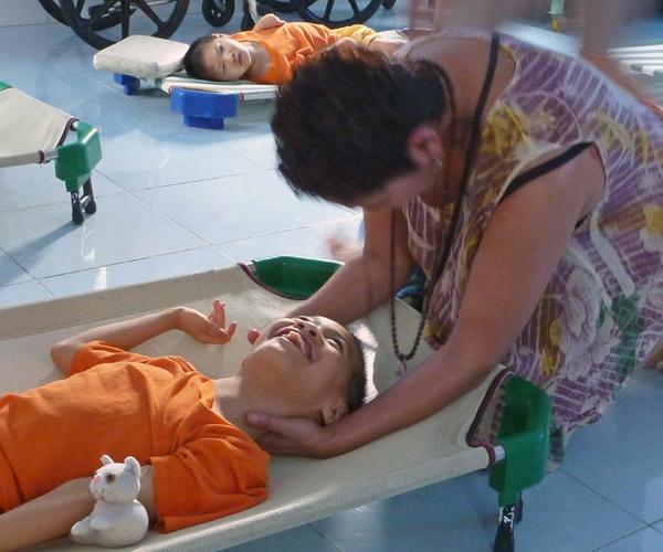 a volunteer provides therapeutic massage to an orphan with physical disabilities in Vietnam