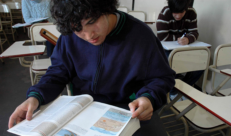 A male university student reading in class