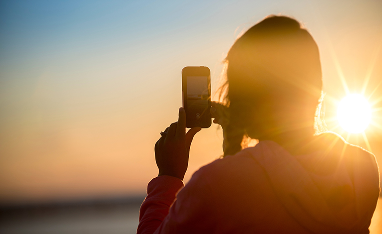 Girl taking a photo of a sunrise