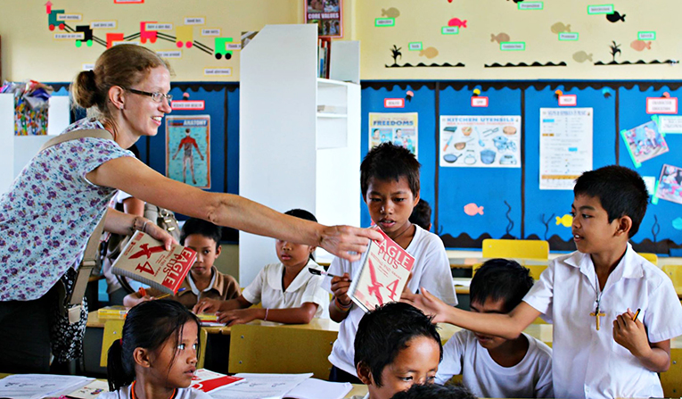 A teacher giving books to students