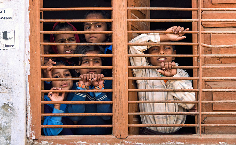 Indian children looking outside a window