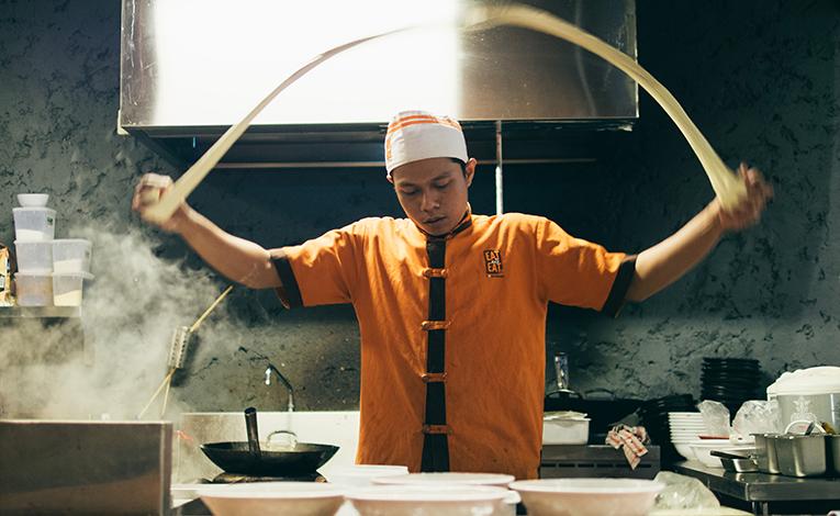 Man preparing noodles in an Asian restaurant kitchen