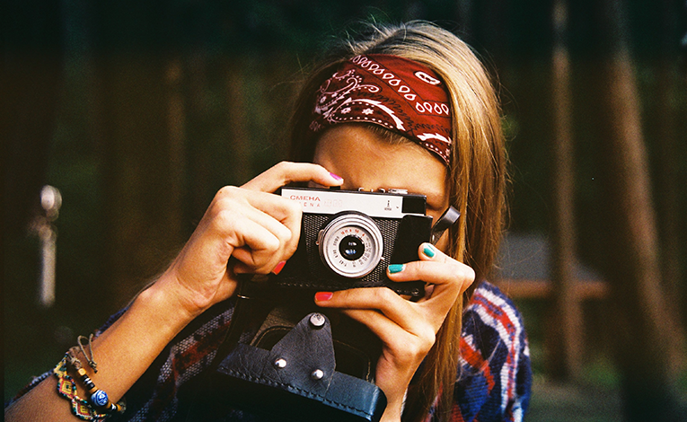 Girl snapping a photo on a film camera