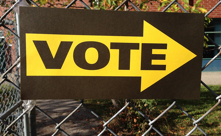 sign pointing to polling place vote