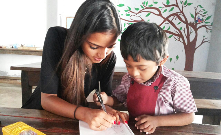 Volunteer tutoring a child in India