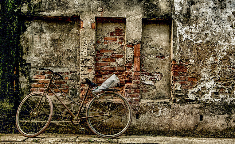 bike leaning on brick wall in vietnam