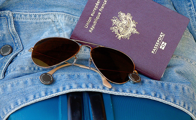 Suitcase with jean jacket, French passport, and aviator sunglasses