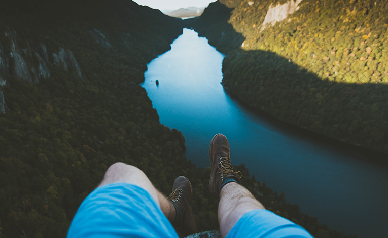 Man wearing hiking boots hanging his feet over a cliff