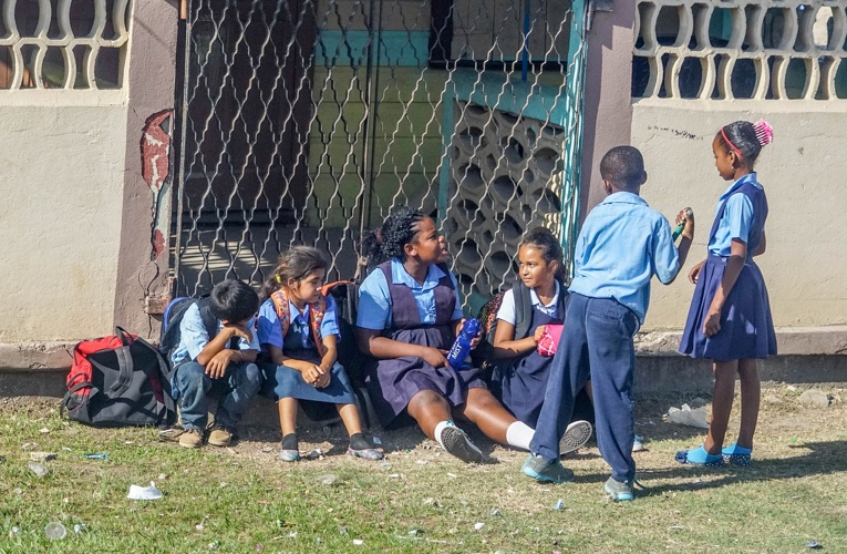 School children in Belize sitting on the grass outside their school