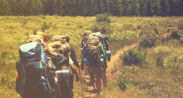 Backpackers walking through a meadow