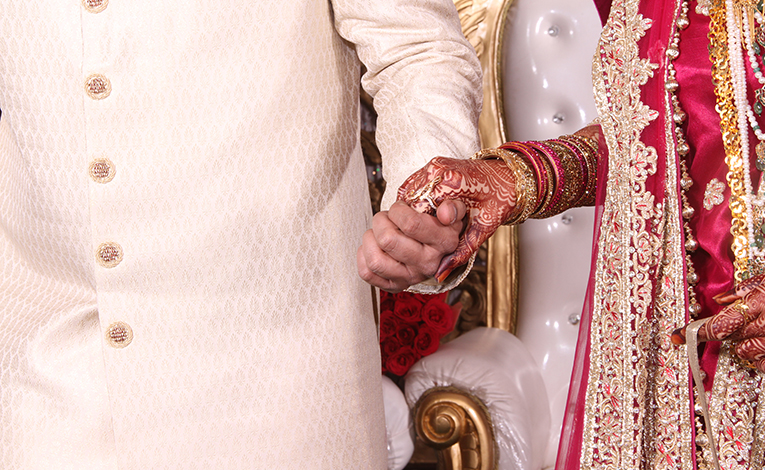 Man and woman holding hands at a wedding ceremony