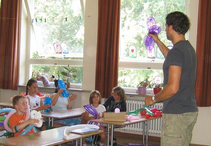 Teacher in front of students with balloons and balloon animals everywhere
