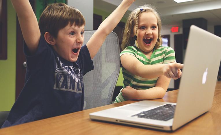 Kids cheering at a computer screen