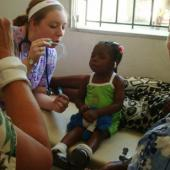 Entertaining a young Haitian girl whose mom was getting treated for dehydration at a clinic in Dumay. Volunteerism in health and community development are in high demand in Haiti.
