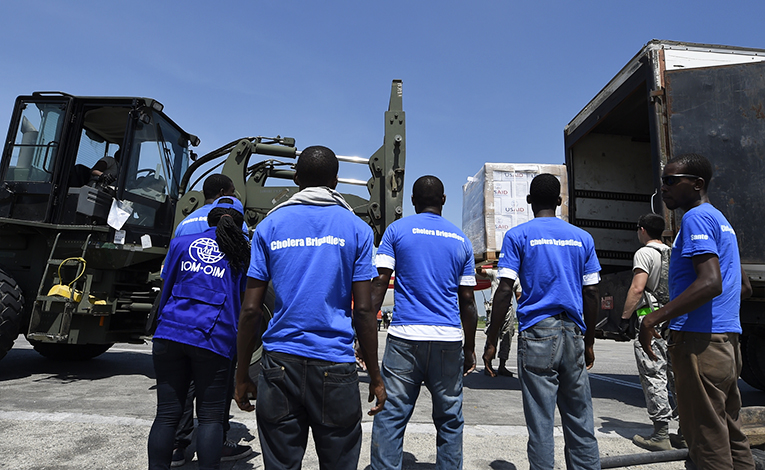 Volunteers waiting to distribute newly-arrived USAID shipments in Haiti
