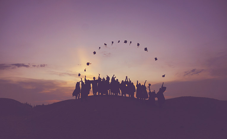 Silhouettes of graduates throwing their caps into the air