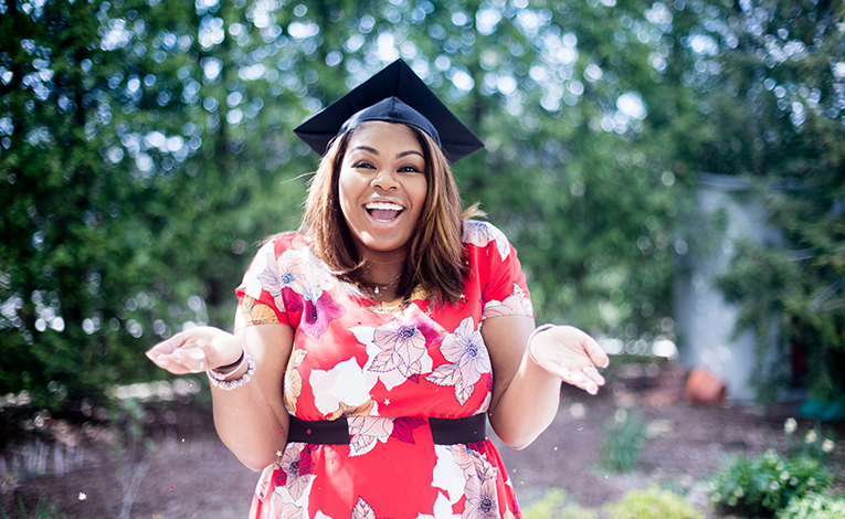 shrugging and smiling woman in a graduation cap