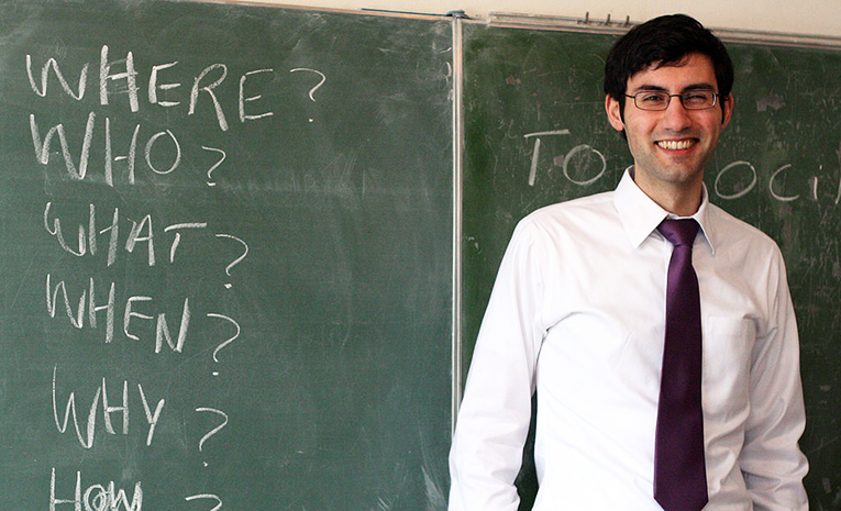 Teacher in front of a chalk board