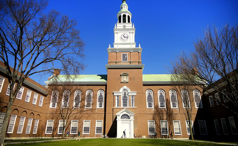 Dartmouth college campus clock tower with a green quad and blue skies