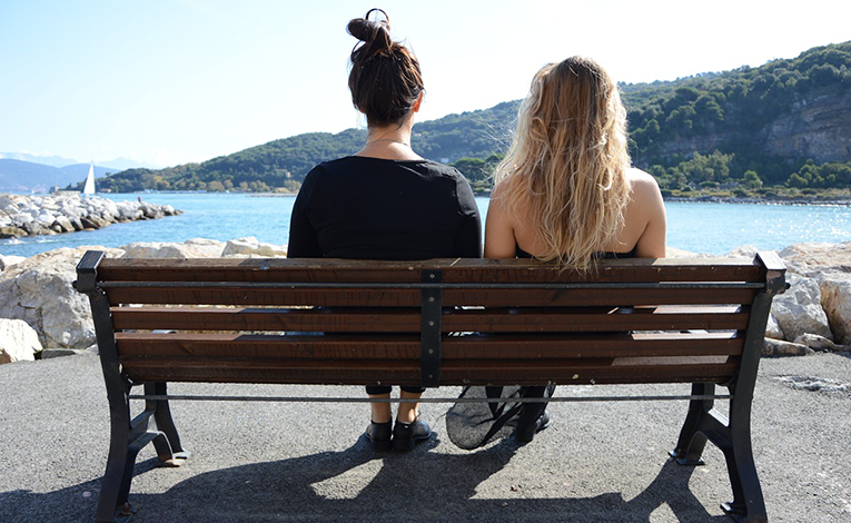 Women on a bench facing the sea
