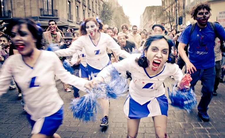 Zombie cheerleaders running down a street