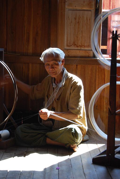 Man spinning silk in Myanmar
