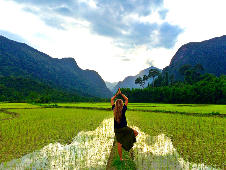 Girl doing a yoga pose by a rice field