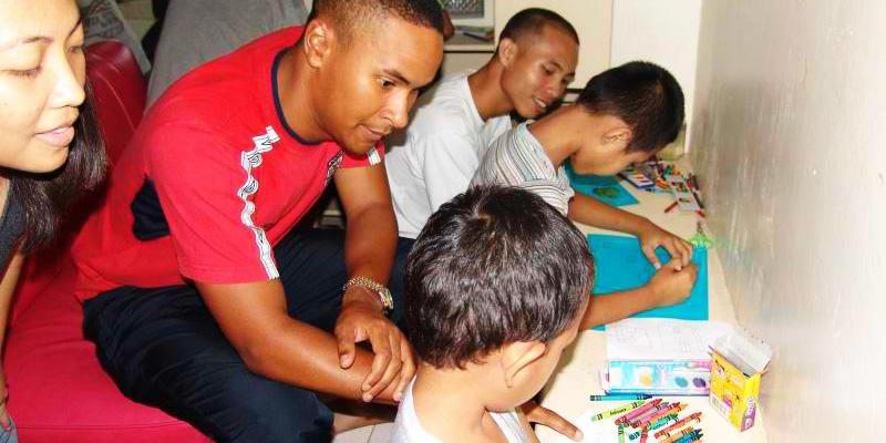 Volunteer teachers working on an art project with students