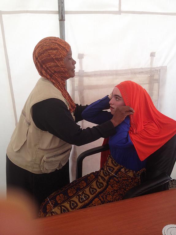 Woman putting a hijab on a teenage girl