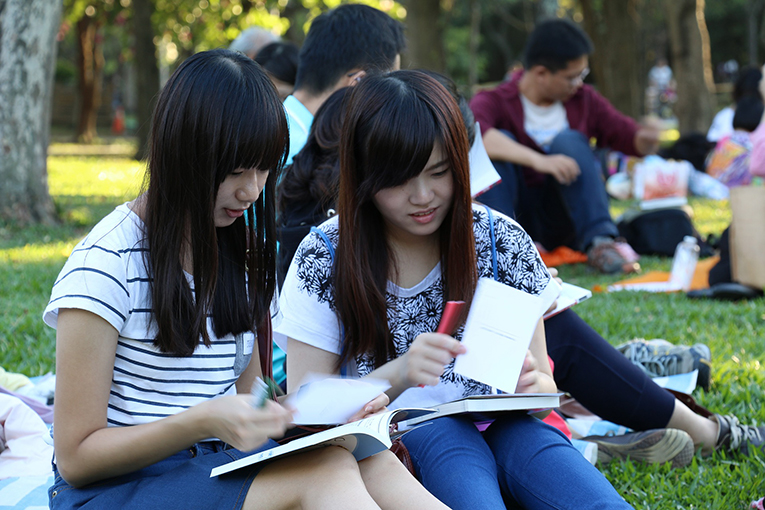 Asian students reading a textbook in a park